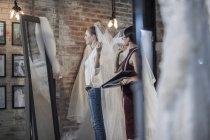Créateur de robe de mariage et mariée debout dans bridal boutique — Photo de stock
