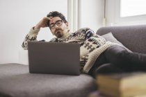 Man lying on a couch looking at laptop — Stock Photo
