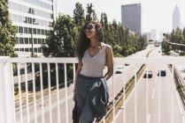 Jeune femme souriante debout sur le pont — Photo de stock