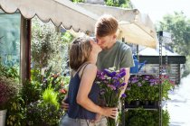 Kissing couple in front of flower stall — Stock Photo