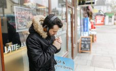 UK, London, man with headphones standing in front of window display lighting a cigarette — Stock Photo