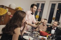 Cheerful group of friends opening champagne on New Year's Eve — Stock Photo