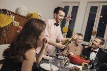 Grupo alegre de amigos abrindo champanhe na véspera de Ano Novo — Fotografia de Stock