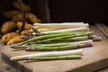 Asperges vertes et blanches sur planche de bois — Photo de stock