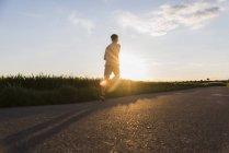 Молодой человек бегает против солнца — стоковое фото
