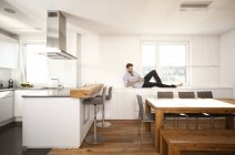 Man lying on sideboard in his open plan kitchen using smartphone — Stock Photo