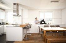 Homme allongé sur le buffet dans sa cuisine ouverte à l'aide de smartphone — Photo de stock