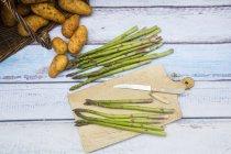 Couteau et asperges vertes — Photo de stock