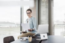 Businesswoman reading paper in office — Stock Photo