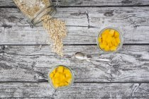 Two glasses of overnight oats with diced mango on wood — Stock Photo