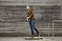 Smiling man with coffee to go on skateboard in front of wooden wall — Stock Photo