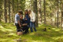 Vater und seinen drei Kindern in den Wald Pilze sammeln — Stockfoto