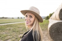 Woman wearing hat standing in countryside — Stock Photo