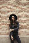 Giovane donna alla moda indossando cappello nero in piedi davanti alla facciata — Foto stock