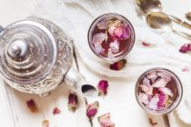 Teapot and two glasses of rose blossom tea with dried rose blossoms — Stock Photo