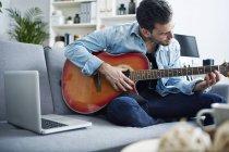 Junger Mann sitzt zu Hause auf Couch und spielt Gitarre neben Laptop — Stockfoto