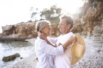 Active cute senior couple hugging and looking at each other on beach — Stock Photo