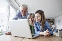 Abuelos y su nieta se divierten con el ordenador portátil en casa - foto de stock