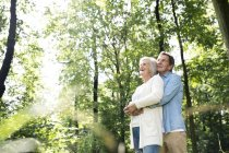 Active cute senior couple hugging together at park — Stock Photo