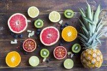 Ananas, Blaubeeren, Wolfbeeren, Kiwis und Zitrusfrüchte in Scheiben auf Holz — Stockfoto