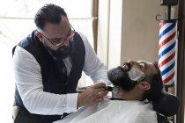Barber putting shaving foam in man beard — Stock Photo