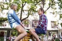 Счастливая пара мило старший, сидя на качелях на площадке — стоковое фото