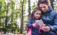Mother and little daughter playing with smartphone in the woods — Stock Photo