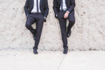 Two businessmen wearing black suits leaning side by side against wall — Stock Photo