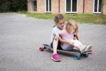Дві сестри, сидячи на longboard на відкритому повітрі — стокове фото