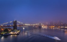 USA, New York City, view to Brooklyn Bridge in the fog at night — Stock Photo