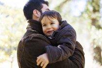 Портрет усміхнений маленький хлопчик на батьків зброї — стокове фото