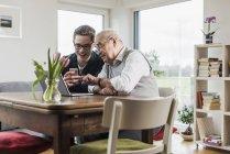 Senior mit Enkel sitzt mit Laptop und Smartphone am Wohnzimmertisch — Stockfoto