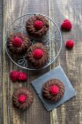 Mini cakes with raspberries on cooling grid and slate — Stock Photo