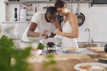 Счастливый молодая пара, подготовка вафлями в кухне — стоковое фото