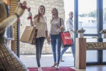 Two friends with shopping bags on a shopping spree — Stock Photo
