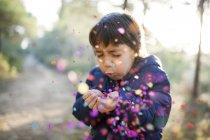 Menino soprando confete no ar — Fotografia de Stock
