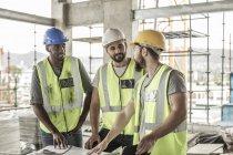 Строители обсуждают на строительной площадке — стоковое фото