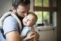 Father cuddling with baby in baby carrier — Stock Photo