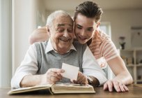 Grandfather and grandson watching old photographies together — Stock Photo