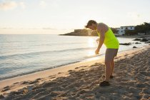 Jogger with water bottle standing at beach — Stock Photo
