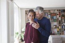 Feliz maduro adulto caucásico pareja abrazos en casa - foto de stock