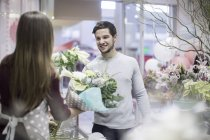 Man buying flowers in flower shop — Stock Photo