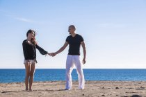 Happy couple standing hand in hand on the beach — Stock Photo