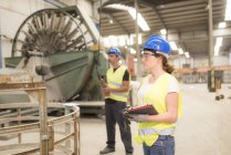 Woman standing in factory hall with man using control — Stock Photo