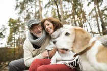 Happy senior couple with dog in nature — Stock Photo