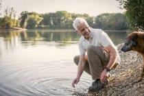 Senior hombre jugando con el perro en un lago - foto de stock