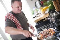 Portrait of Man cooking in kitchen — Stock Photo