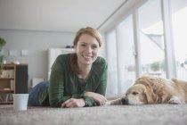 Woman relaxing on floor with sleeping dog — Stock Photo