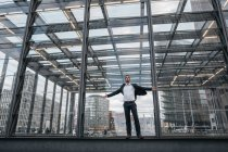 Germany, Berlin, businessman with arms outstretched standing in front of glass pane — Stock Photo