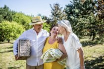 Happy elderly friends walking on a meadow with blanket and picnic basket — Stock Photo